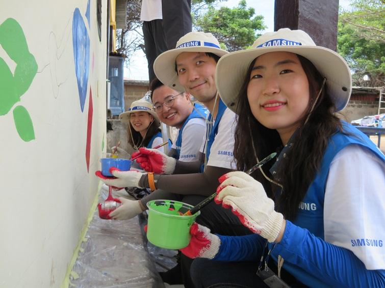 벽화를 그리고 있는 삼성전자 임직원들의 모습