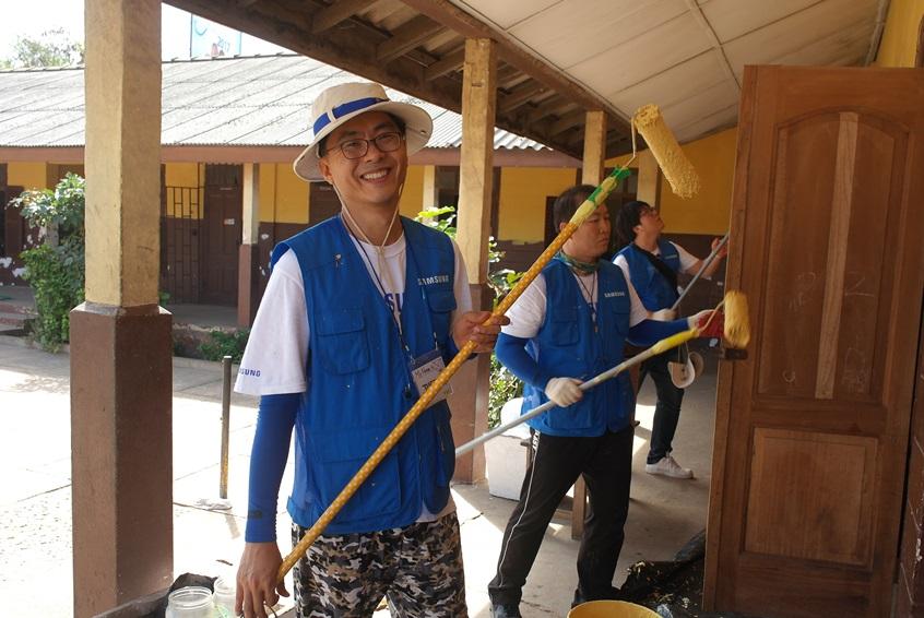 학교 외벽을 도색하고 있는 삼성전자 임직원들의 모습