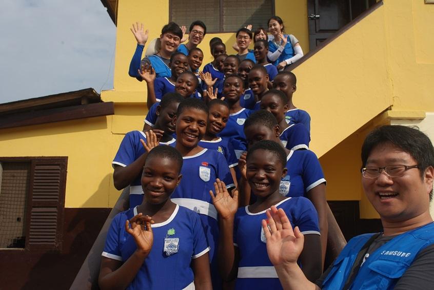 아이들과 함께 밝게 웃으면 손을 흔드리는 삼성전자 임직원들