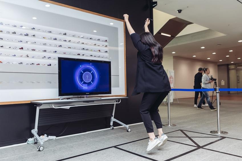 ▲ 기어 S3은 이용자의 모션에 따라 반응한다. 기어 S3이 팔을 높게 들라는 지시를 따르는 참가자의움직임을 포착하여 앞의 TV 화면에 현 상태를 나타내주고 있다