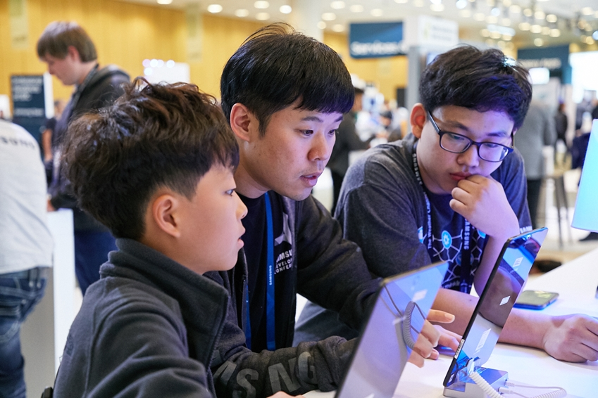 ▲삼성전자 사회공헌사무국 이강민씨가 2016년 주니어소프트웨어 창작대회 수상자들에게 현재 전시 중인 모바일 코딩 앱을 설명하고 있다