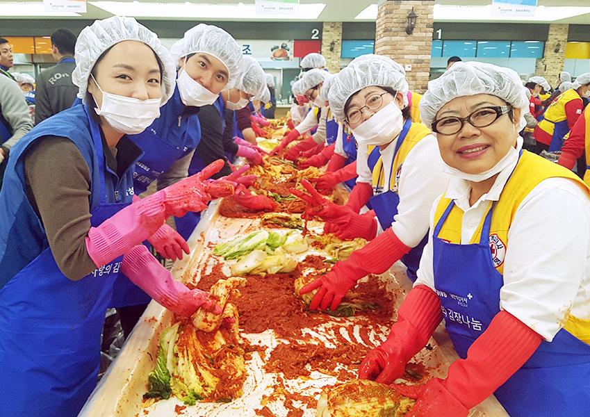 ▲ 삼성전자 임직원들과 대한적십자사 자원봉사자들이 힘을 모아 김치를 완성하고 있다