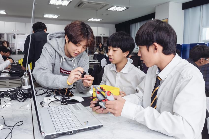 로봇 꿈나무 교실에서 학생들을 가르치는 봉사자