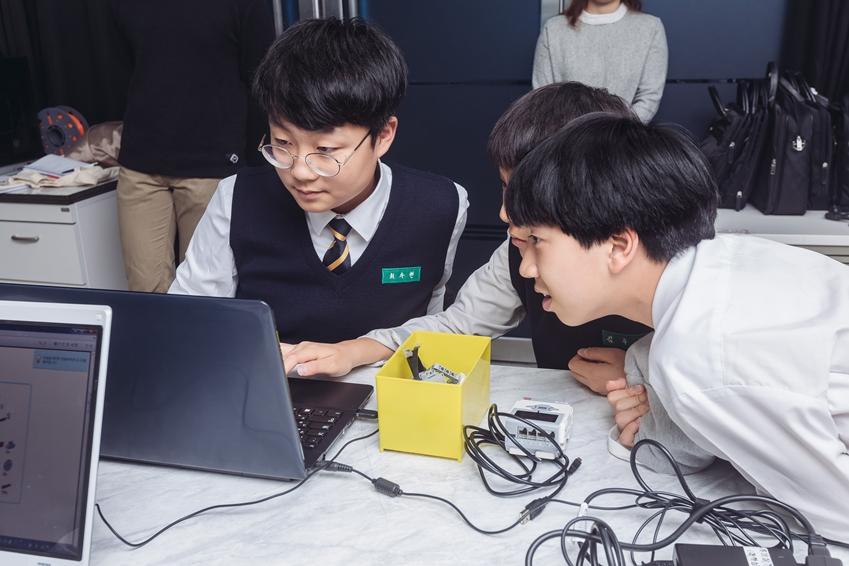 친구들과 함께 로봇 프로그래밍에 열중하는 학생들