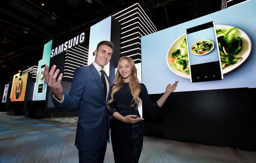 ▲삼성전자는 9일부터 12일까지 미국 라스베이거스에서 열리는 세계 최대 전자 전시회 CES 2018에서 사물인터넷(IoT)•인공지능(AI)을 기반으로 한 미래 라이프스타일 솔루션을 대거 공개한다. 삼성전자는 전시장을  '삼성 시티'라는 콘셉트로 구성해 삼성의 IoT•AI에 기반한 혁신 기술이 다양한 제품과 서비스를 연결해 '소비자들의 일상에 의미 있는 변화와 도전을 가능케 한다'는 비전을  거대한 LED사이니지로 구성된 파사드로 표현했다. 삼성전자 모델들이 전시장 입구 대형파사드 앞에서 환영의 포즈를 취하고 있다.