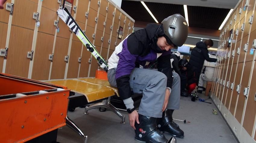 장비를 챙겨 스키를 탈 준비 중, 손목에 기어 스포츠가 착용되어있다