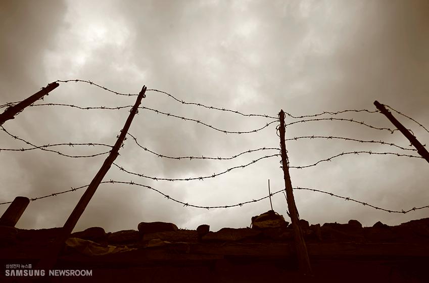 철조망과 음산한 하늘 모습이 전쟁을 연상케 한다