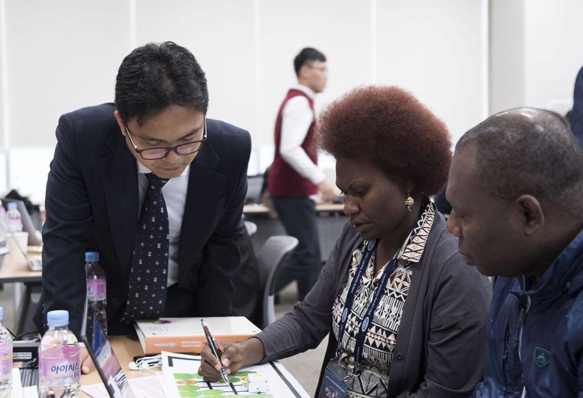 서성원 교사가 APEC 단원들에게 미니로봇 작동법을 설명하고 있다