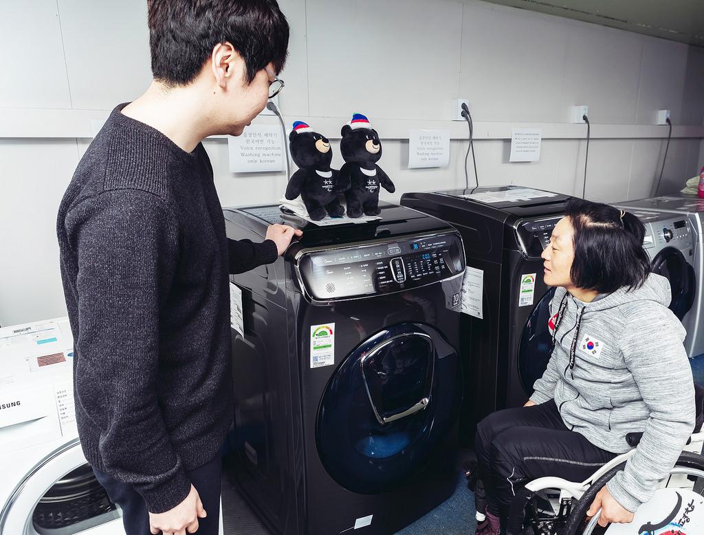 ▲ 크로스컨트리 국가대표 이도연 선수(오른쪽)가 지난달 평창 동계패럴림픽 선수촌에서 인공지능(AI) 기반 음성인식 기술을 적용한 플렉스워시 세탁기를 사용해보고 있다