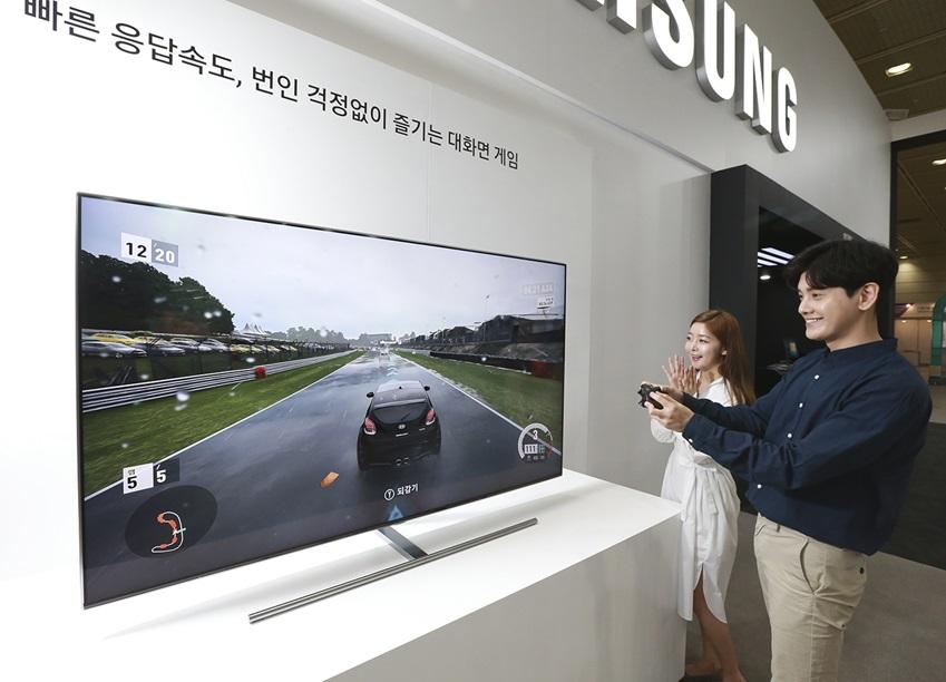 삼성전자가 23일부터 26일까지 서울 코엑스(COEX)에서 열리는 '월드 IT쇼 2018(World IT Show 2018)'에 참가해 최신 전략 제품들을 선보이고 혁신적 스마트 라이프 경험을 제공한다. 삼성전자 모델들이 삼성 QLED TV의 대화면에서 게임을 즐기고 있다.