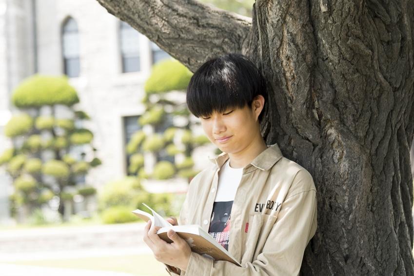 나무에 기대어 책을 보는 예기 학생