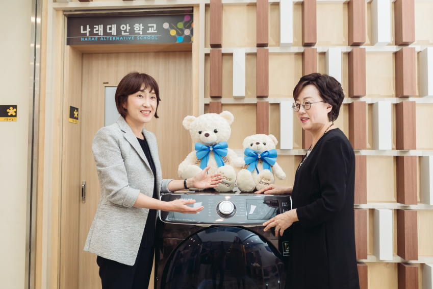 삼성전자 김현숙 상무(좌측)가 애란원 강영실 원장에게 14kg 대용량 건조기 '그랑데'의 사용법을 소개하고 있다.