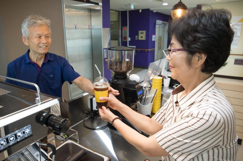 아산시노인종합복지관 회원이 어르신 바리스타에게 음료를 주문하고 있다.