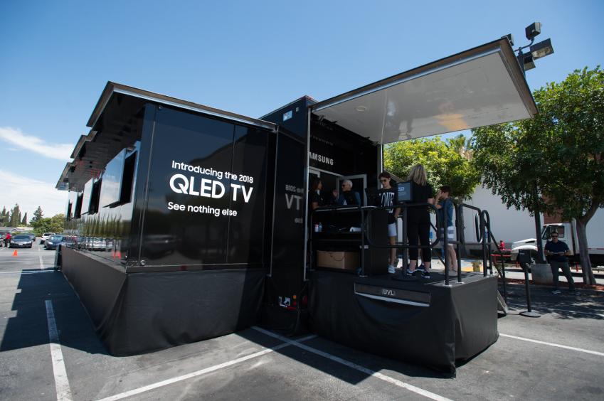 삼성전자가 마이크로소프트(MS) 콘솔 게임기 '엑스박스(Xbox)'와의 협업을 통해 대형 트럭에 'QLED TV' 6대와 '엑스박스 원 엑스(Xbox One X)' 게임기로 구성된 이동형 체험관을 마련해 미국 게이머들을 대상으로 제품의 특장점을 직접 경험해 볼 수 있게 하며 QLED TV의 우수성을 알린다. 이 체험관은 로스엔젤레스를 시작으로 샌프란시스코·샌디에고·시애틀·라스베이거스·피닉스·달라스·휴스턴 등 미국 내 14개 주요 도시를 돌며 8월 초까지 진행될 예정이다. 대형 트럭에 마련된 삼성 QLED TV 이동형 체험관 전경(* 뉴 레볼루션 미디어 제공)