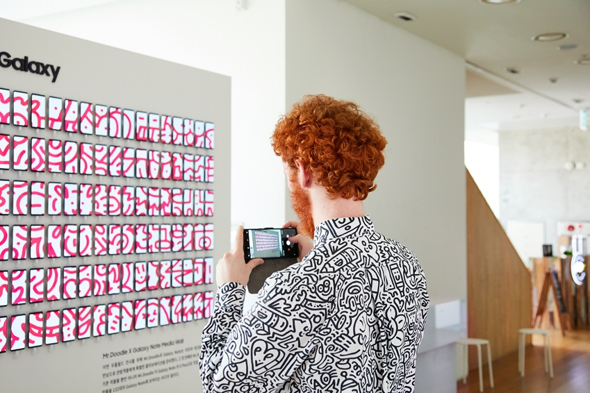 ▲ 미스터 두들이 갤럭시 노트 미디어 월에 전시된 자신의 디지털 작품을 카메라에 담고 있다. (사진제공: 주관사 시니트)