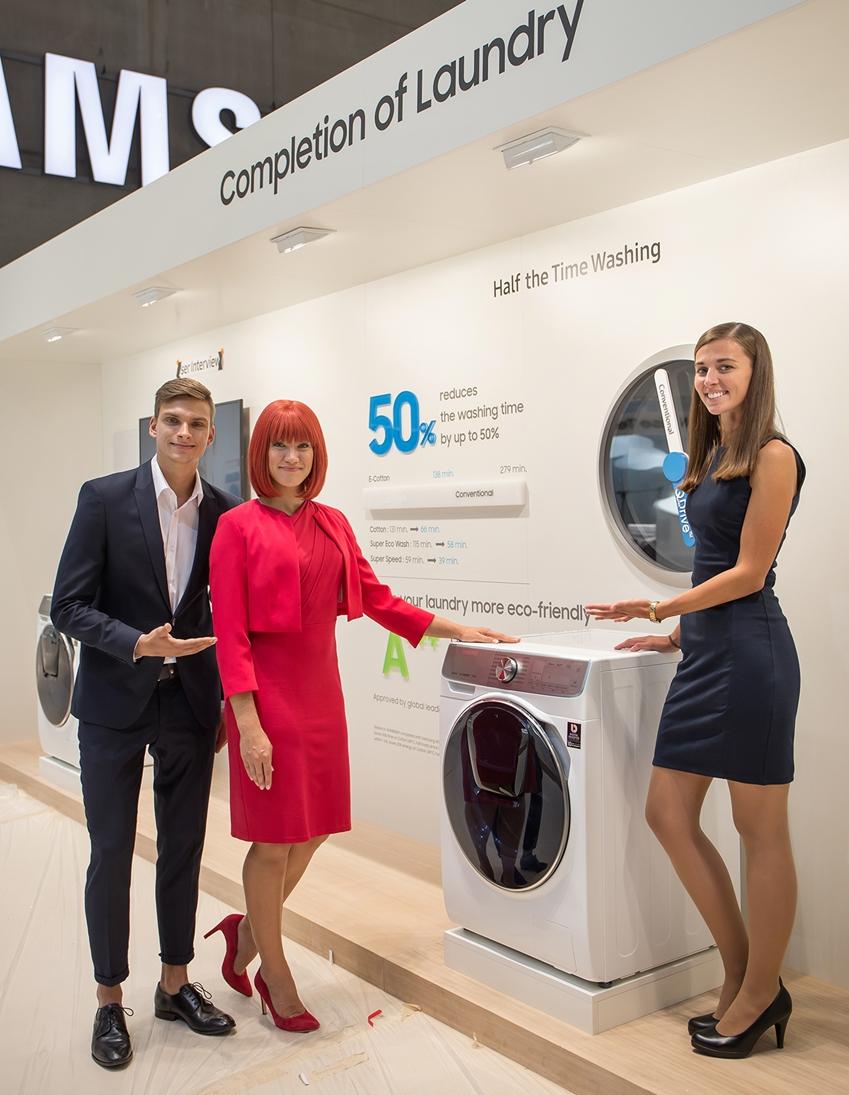IFA 2018 공식 모델과 삼성전자 모델이 드럼 세탁기에 전자동 세탁 방식을 접목해 세탁 시간을 절반 가까이 줄인 삼성전자 '퀵드라이브(Quick Drive)'를 소개하고 있다.