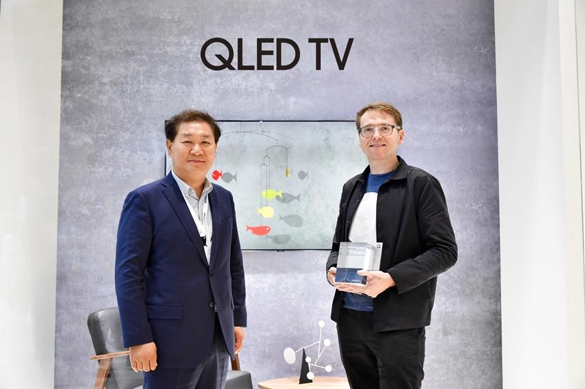 삼성전자가 영국 디자인 전문 매체 '디진(Dezeen)'과 공동 주최한 'QLED TV 매직 스크린 공모전'에 대해 8월 31일(현지 시간) 유럽 최대 가전 박람회인 IFA 2018에서 최종 우수작 시상을 진행했다. 시상식에서 이번 공모전 대상을 수상한 영국과 덴마크의 디자인팀, '스위프트 크리에이티브스(Swift Creatives)'의 매튜 커커릴(Matthew Cockeril) 디자이너가 삼성전자 영상디스플레이사업부의 한종희 사장과 기념 촬영을 하고 있다.