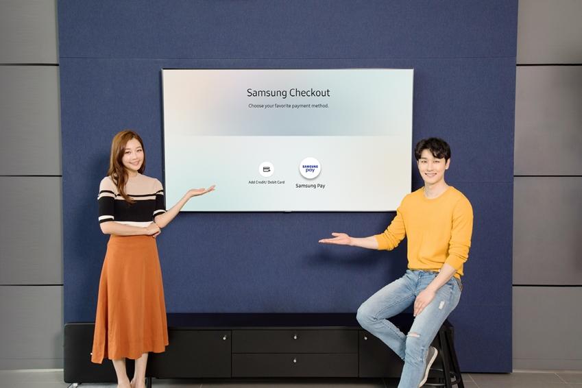 삼성디지털프라자 용인 구성점에서 모델들이 2018년형 삼성 QLED TV 내에 탑재된 T-커머스(T-Commerce) 전용 결제 시스템 '삼성 체크아웃(Samsung Checkout)'에 도입된 '삼성페이' 간편결제 서비스를 소개하고 있다.