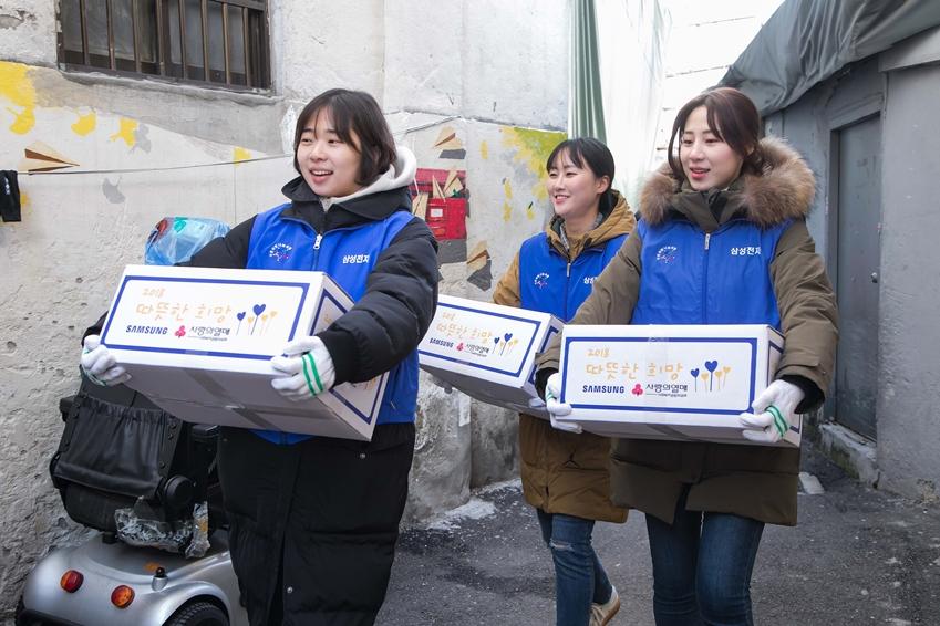 5일 삼성전자 임직원들이 서울 동대문구에 위치한 쪽방을 찾아 거주하는 어르신들에게 전달할 생필품 세트를 나르고 있다.