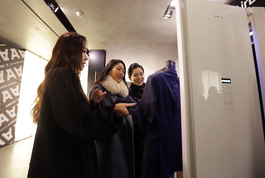 ▲의류 안까지 관리할 수 있는 에어드레서의 안감케어 옷걸이를 참석자들이 세심하게 살펴보고 있다.