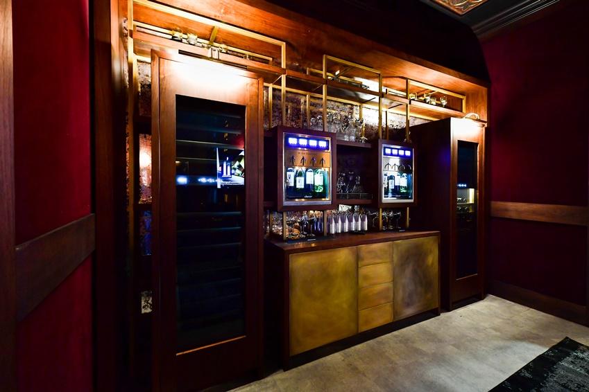 ▲ 고급스러운 바(Bar)가 집 안으로 들어왔다. 와인 톤의 벽지와 어우러지는 짙은 원목 느낌의 가구와 골드 컬러의 철재 장식장은 비밀스럽고 우아한 공간을 완성한다.
