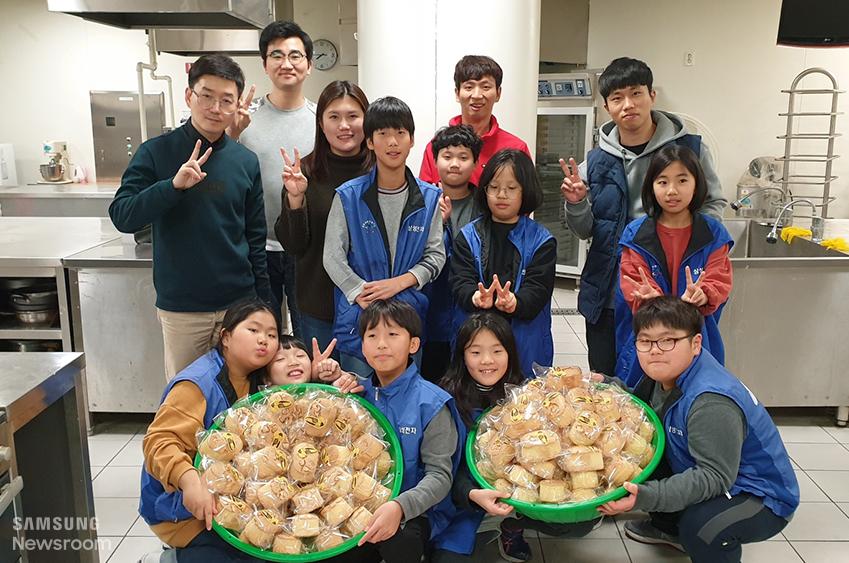 ▲ 진원 씨는 매주 화요일마다 빵을 만들어 독거노인들에게 드린다. 함께 만든 빵을 들고 포즈를 취한 진원 씨(사진 왼쪽에서 6번째)와 공부방 아이들