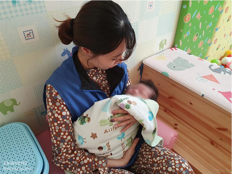 아기를 안고 있는 봉사단
