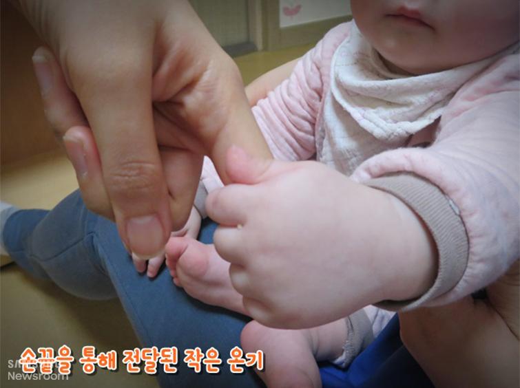 아기의 손을 잡고 있는 어른 손 /  손끝을 통해 전달된 작은 온기