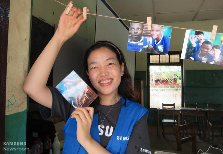 해외봉사에서 만난 아이들의 사진을 들고 있는 홍자경씨