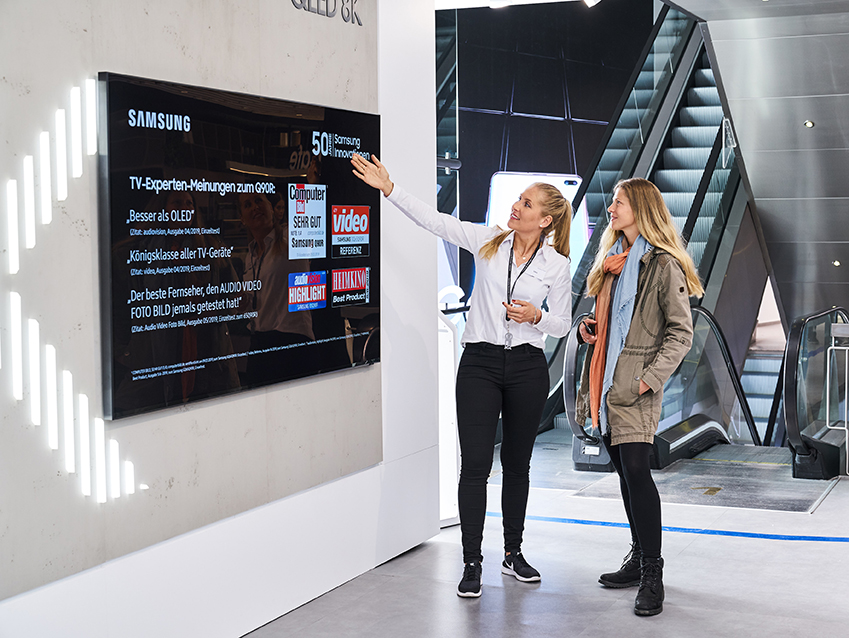 독일 프랑크푸르트 시내에 위치한 삼성 쇼케이스 매장에서 판매 직원이 고객에게 영상·음향기기 전문 매체들로부터 호평받은 QLED TV를 소개하고 있다.
