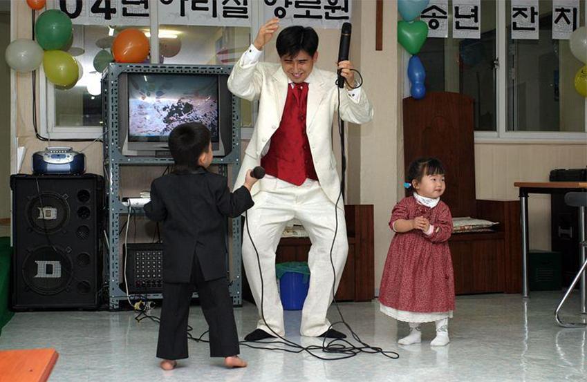 2004년 아리실복지원 송년 행사. 김진묵 씨가 아들과 함께 턱시도를 입고 트로트를 부르고 있다. 시간이 흘러 이제 김진묵 씨의 아들은 대학생이 됐다.