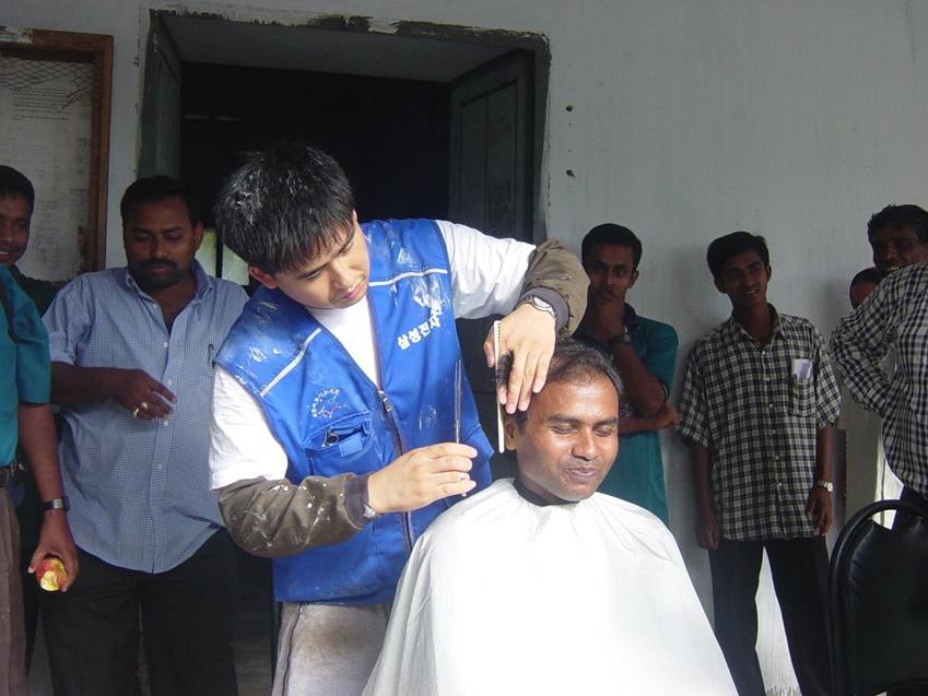 2003년 방글라데시의 한 마을에서 이발 봉사를 하고 있는 김진묵 씨. 주민들이 줄을 서서 머리를 자를 정도로 그의 '한국식 커트'가 크게 인기를 끌었다.