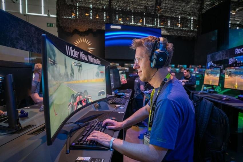 △ '게임스컴 2019' 삼성부스를 찾은 관람객이 49인치 CRG9의 넓은 32:9 화면으로 레이싱 게임을 즐기고 있다