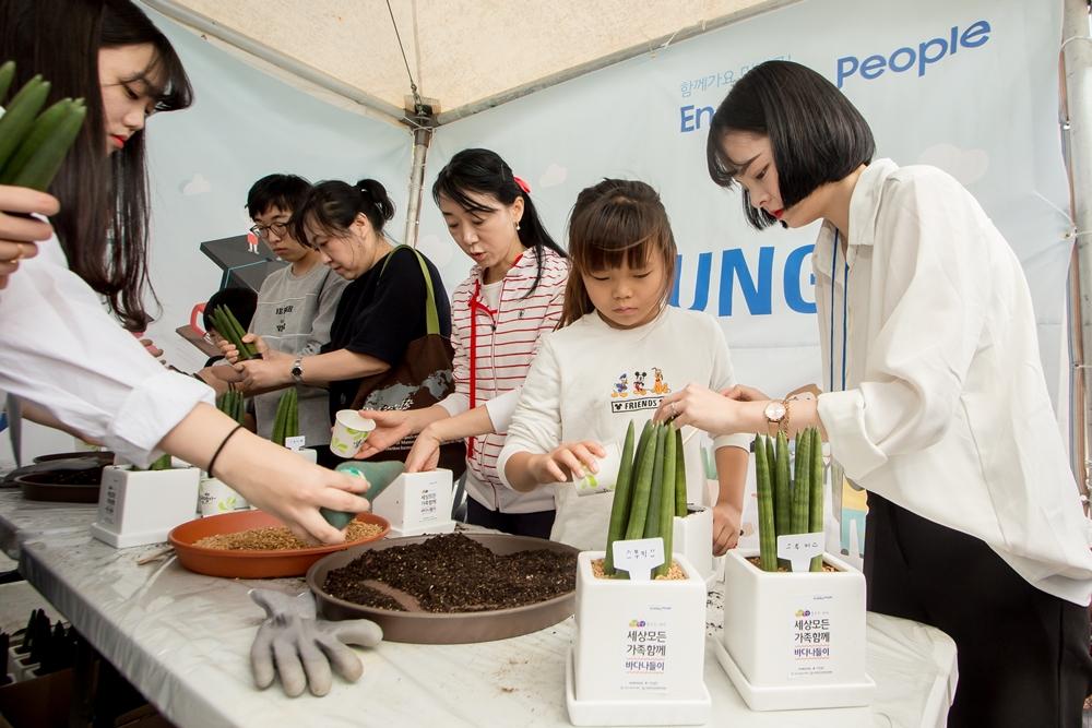 6일 부산에서 열린 '세상모든가족함께 바다 나들이' 행사에 참여한 시민들이 삼성전자 청소년자립지원 사업 소개 부스에서 화분만들기 체험을 즐기고 있다.