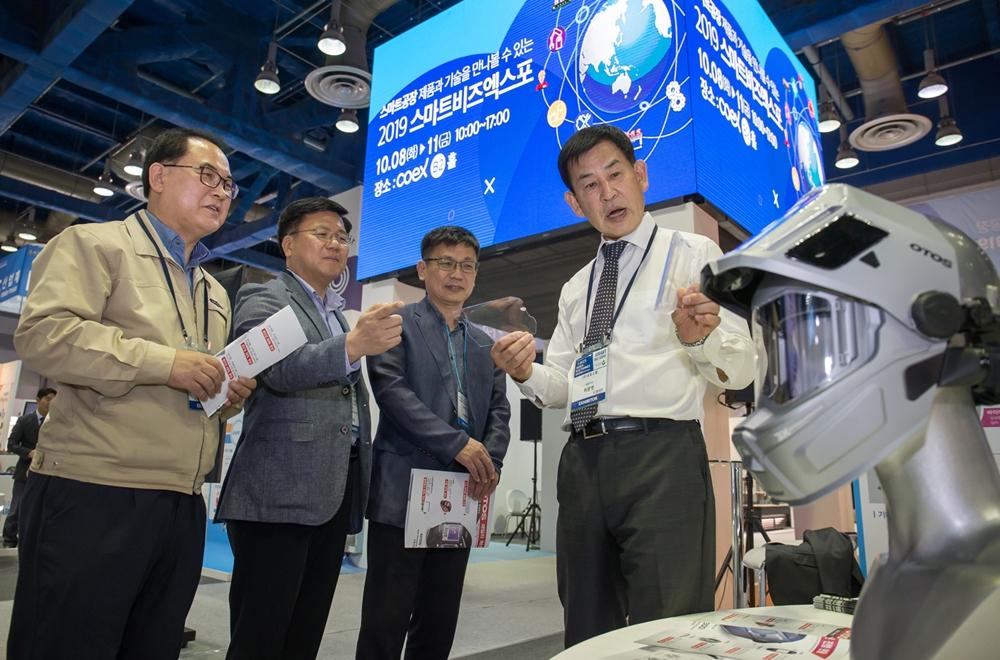 8일 서울 코엑스에서 열린 '2019 대·중소기업 상생협력 스마트비즈엑스포'에 참가한 산업용 안전 보호구 제조 기업 '오토스윙'의 허문영 대표(맨 오른쪽)가 관람객들에게 제품을 소개하고 있다.