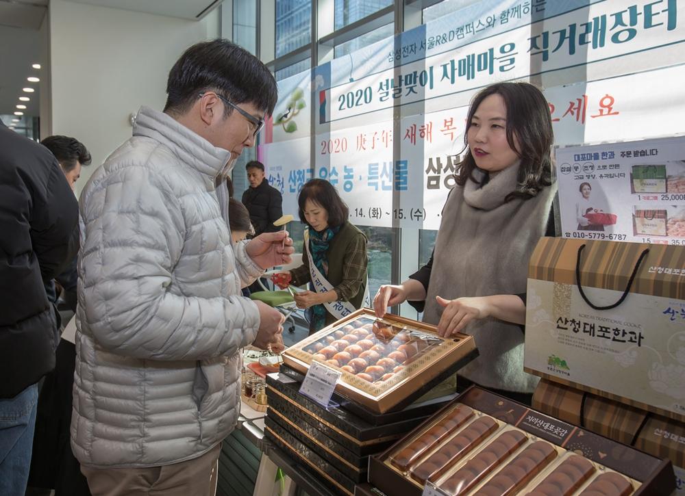 삼성 서울R&D캠페스에서 설을 앞두고 열린 직거래 장터에서 삼성전자 임직원들이 자매마을과 중소기업이 생산한 농축수산물을 구매하고 있다.