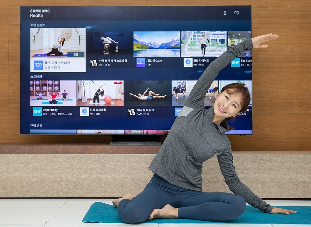 삼성전자 모델이 2020년형 삼성 스마트 TV용 '삼성 헬스' 앱으로 홈 트레이닝 영상을 시청하며 동작을 따라 하고 있다.