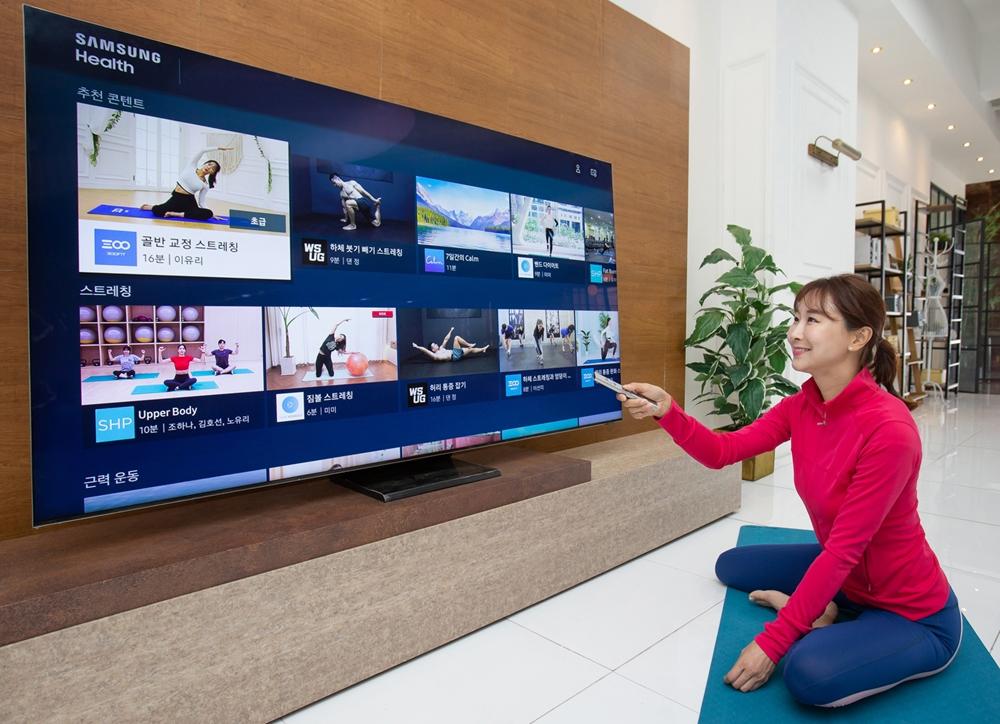 삼성전자 모델이 2020년형 삼성 스마트 TV용 '삼성 헬스' 앱으로 홈 트레이닝 영상을 시청하고 있다. 사진 속 제품은 삼성 QLED 8K QT900 75형 스마트 TV