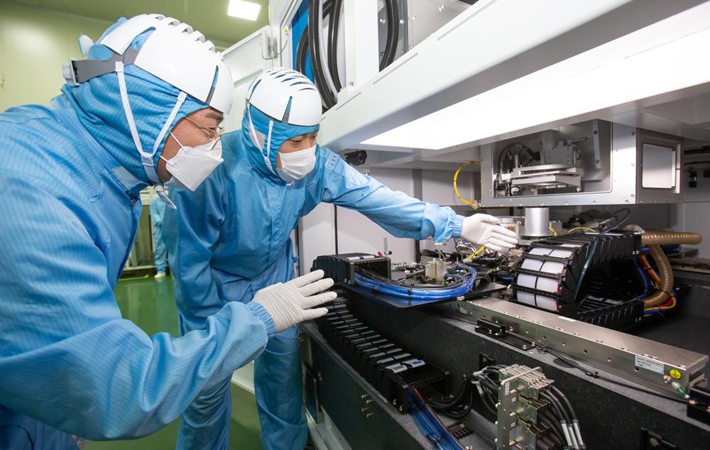 삼성전자 직원(좌)과 이오테크닉스 직원(우)이 양사가 공동 개발한 반도체 레이저 설비를 함께 살펴보고 있다.