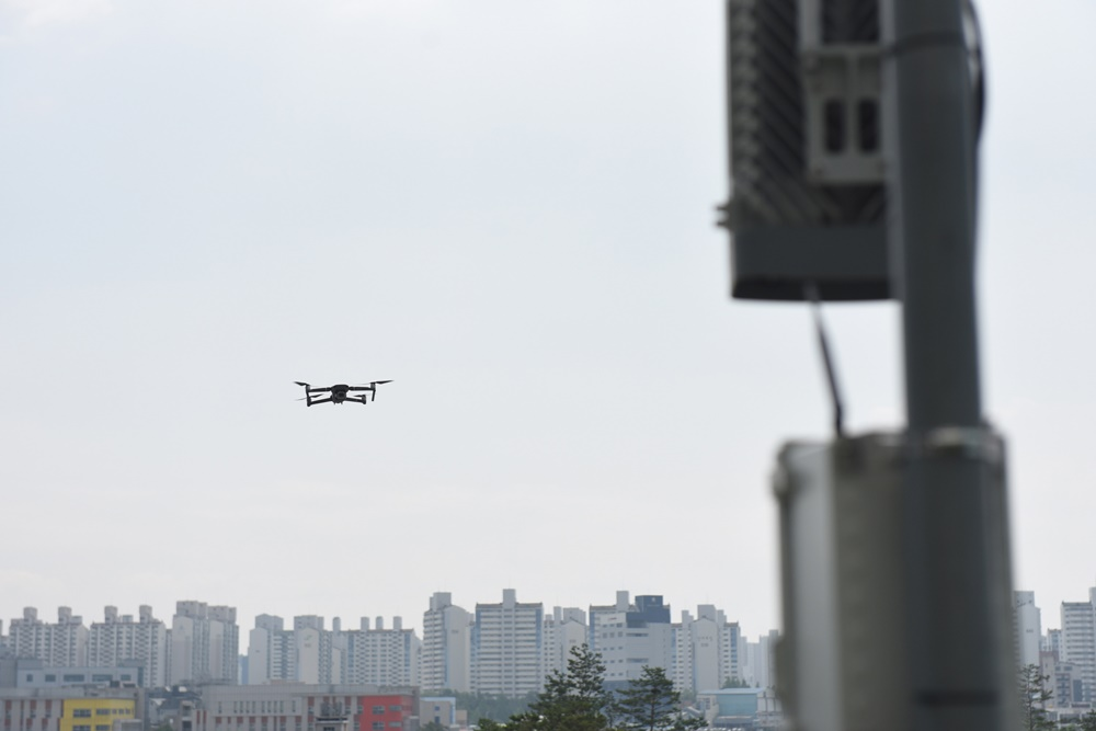삼성 5G 네트워크 성능 최적화 솔루션을 탑재한 드론이 기지국 및 안테나에 근접해 사진을 촬영하고 있는 모습