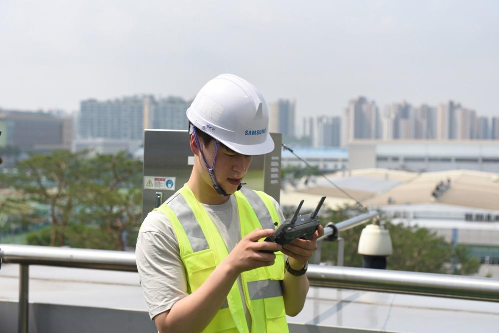 삼성 5G 네트워크 성능 최적화 솔루션 개발자가 기지국과 안테나 각도 측정을 위해 원격에서 드론을 조종하고 있는 모습