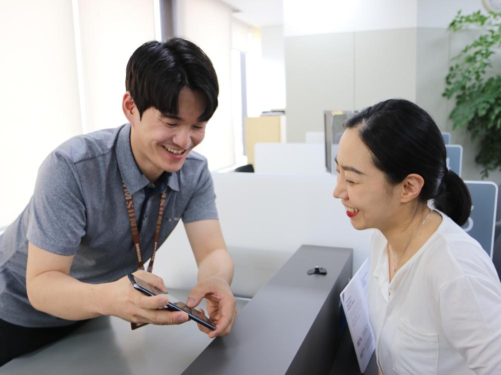 삼성전자서비스 수리 엔지니어가 고객에게 스마트폰 점검 결과를 설명하고 있다.