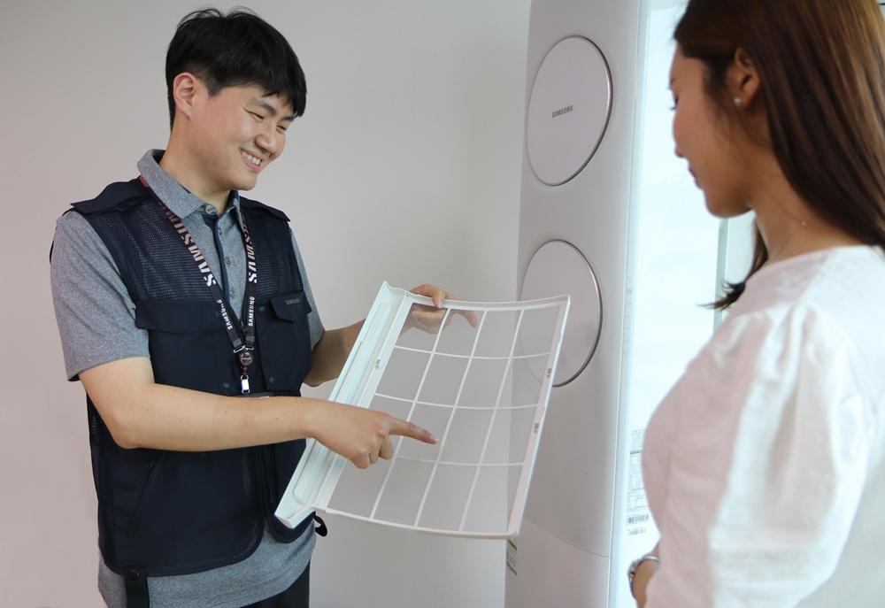 삼성전자서비스 수리 엔지니어가 고객에게 에어컨 필터 관리 방법을 설명하고 있다.