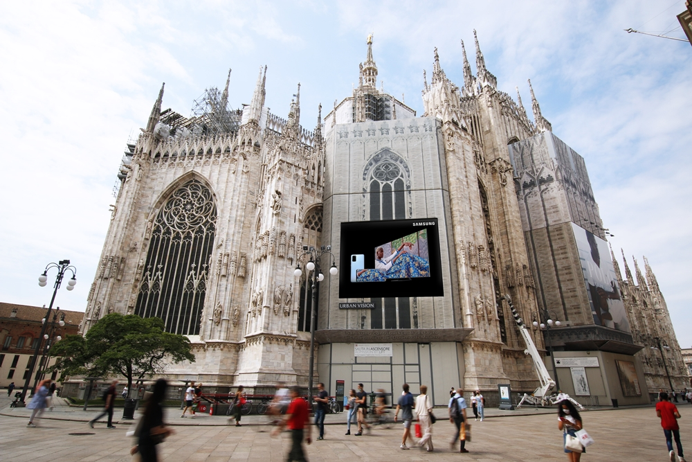 밀라노 두오모 성당에 설치된 삼성전자 대형 LED 사이니지 전경. 그 앞으로 사람들 지나가고 있는 모습