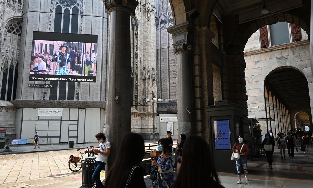 밀라노 건물들 기둥 사이로 보이는 두오모 성당에 설치된 삼성 스마트 LED 사이니지. 화면엔 패션위크 생중계 영상이 방송되고 있다.