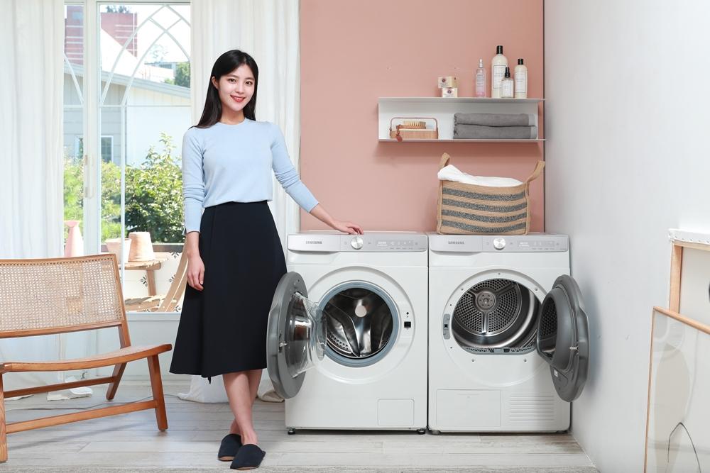 삼성전자 모델이 '그랑데 AI' 10kg 세탁기·9kg 건조기의 문을 열고 소개하고 있다.