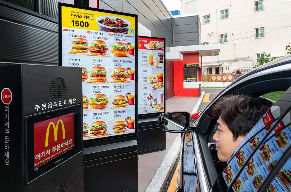 삼성전자 모델이 경기도 고양시에 위치한 맥도날드 고양삼송DT점에 설치된 삼성 스마트 사이니지를 통해 주문을 하고 있다.