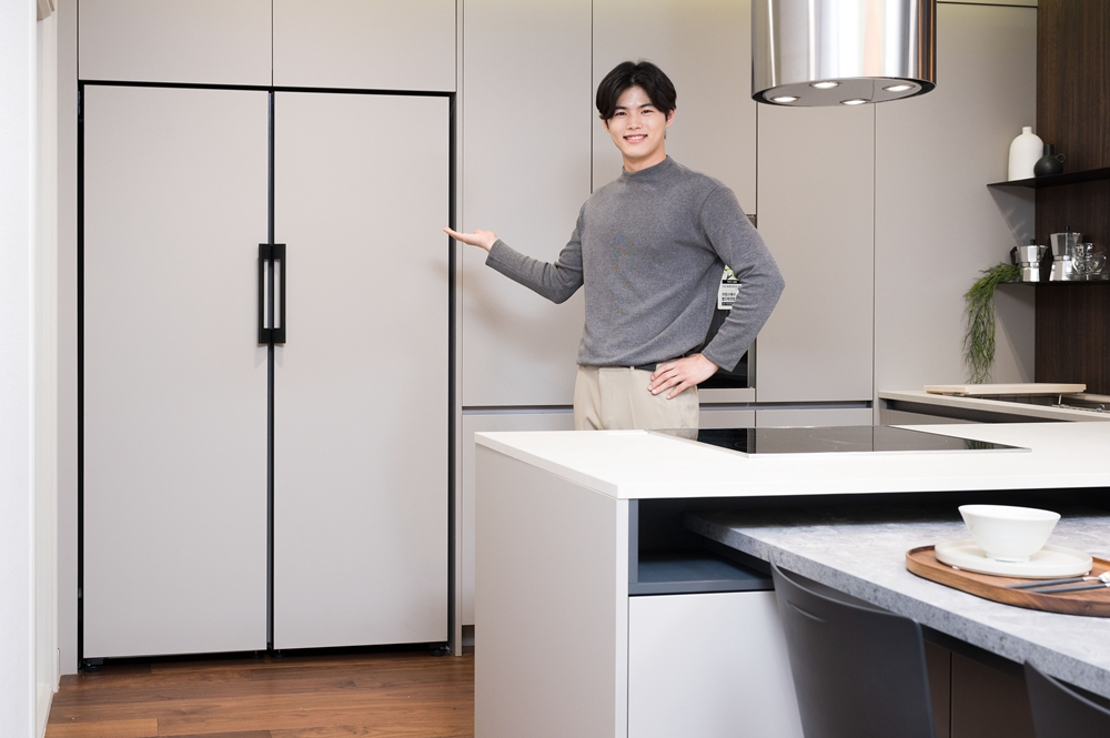 삼성전자 모델이 냉장고를 가리키며 소개하고 있다