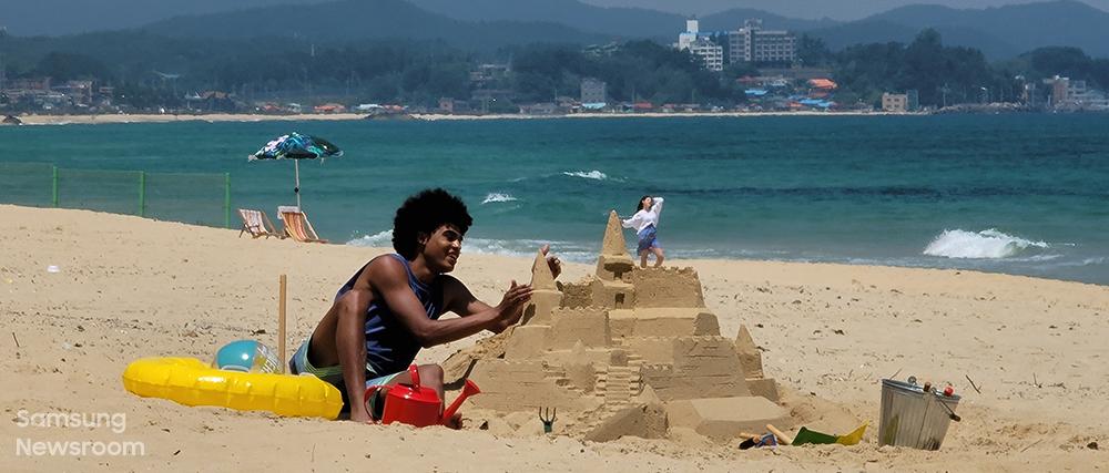 바닷가에서 모래성을 짓고 있는 사람