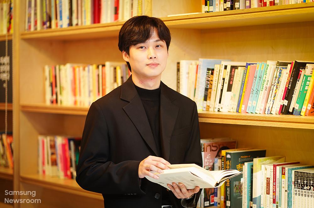 2015년 1회 주소상 우수상을 수상한 김동욱 씨가 책을 손에 들고 정면을 바라보고 있다.